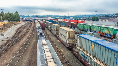 Seattle, Washington, USA - July 27, 2015: trains carry containers and oil tanks stop and wait to unload at Balmer Yard, Seattle, Washington, USA.