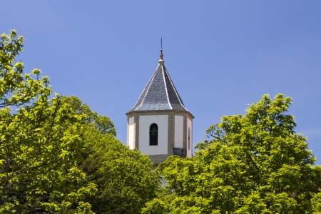 church bell tower with foliage in front and blue sky