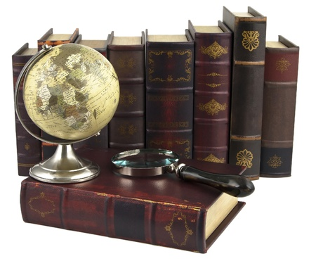 rows of old books with a globe and magnifying glass