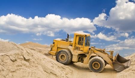 yellow excavator in quarry photo