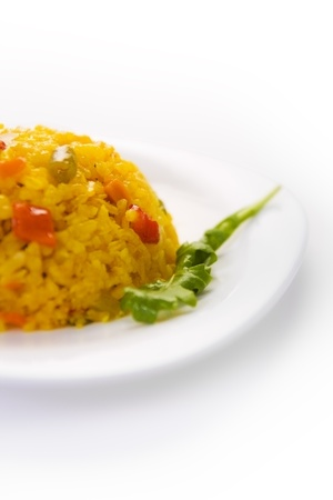 A plate of yellow rice with vegetables Stock Photo