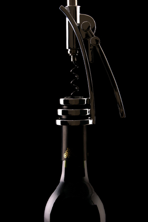 Wine bottle with corkscrew in black background