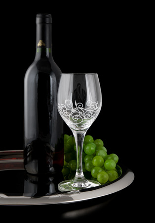 Bottle of wine, cup and grapes in tray