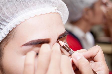 permanent: eye,Asia woman applying permanent make up on eyebrows tattoo. Stock Photo