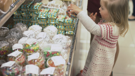 Mother and daughter choosing dragees in packages in the sweets department
