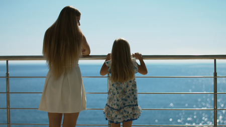 Mother and daughter standing on the outdoor terrace overlooking the sea, rear view Stock Photo - 67345852
