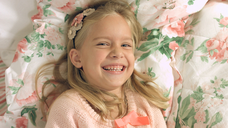 gaily: Adorable little blonde girl lying on the bed and laughing gaily
