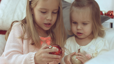 Two little cute sisters playing with Christmas balls while sitting on the couch