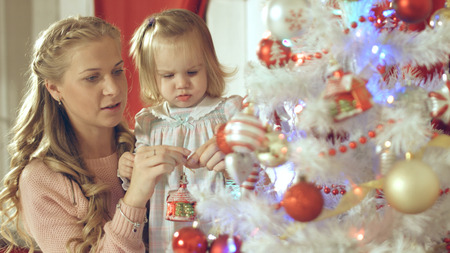Lovely girl hanging christmas ball on the tree with her mother Stockfoto