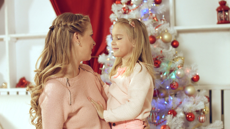 Little girl makes a surprise to her mother for the new year and gives present in red wrapper Stock Photo