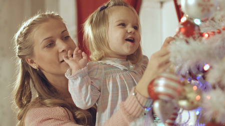 Mother with adorable baby decorate the Christmas tree at home Фото со стока