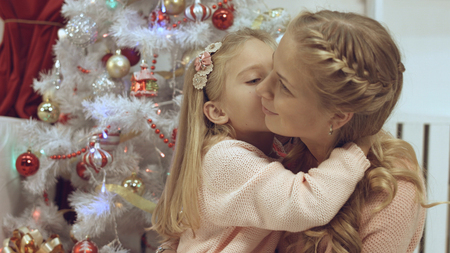 Mother and daughter hug and kiss each other near the Christmas tree