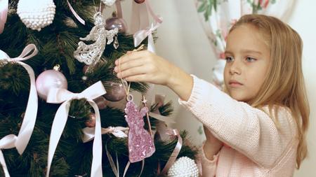 Beautiful blue-eyed girl hangs homemade Christmas toy on Christmas tree