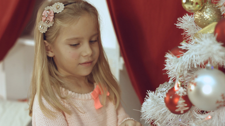 Adorable little blue-eyed girl decorates the Christmas tree with balls
