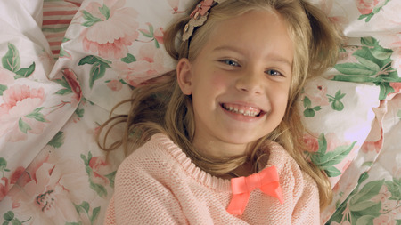 gaily: Adorable little girl lying on the bed and laughing gaily