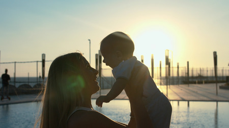 Silhouette of the mother with her little son in her arms at sunset