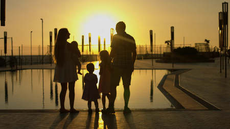 Happy family admiring the sunset by the pool Stockfoto