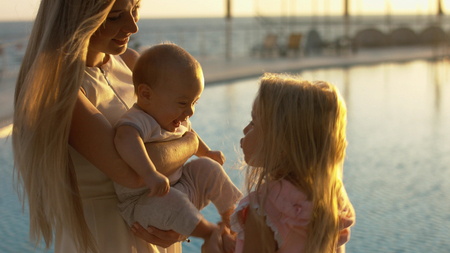 Mother with small children standing by the pool at sunset Stockfoto