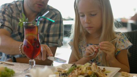 Dad helping daughter to cut the piece of chicken in the Caesar salad Фото со стока