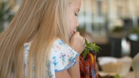 Little white-haired girl drinking berry lemonade with mint from the glass
