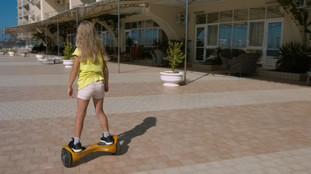Preschooler girl riding on the hoverboard in the park
