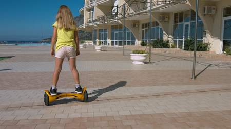 Happy little girl preschooler rides hoverboard in the park