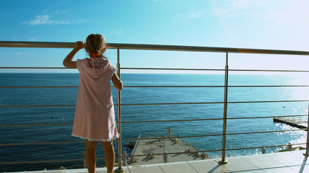 Little girl coming to the railing and looking at the sea