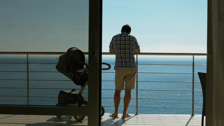 Family with baby carriage standing on the balcony and admiring the view of the sea Stockfoto
