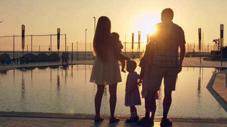 Silhouettes of the happy family with three children admiring the amazing sunset reflected in the surface of the pool in the hotel complex Stockfoto