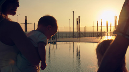 Happy family with three children admiring the sunset reflected in the surface of the pool