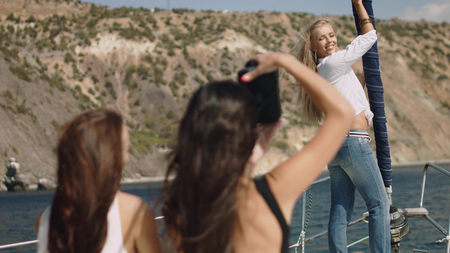 Beautiful girls with camera on the yacht