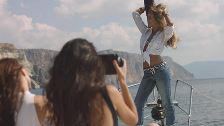 Young girls making picture on the yacht