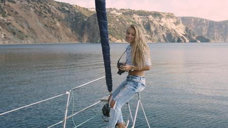 Young woman taking photo of beautiful sea lagoon Фото со стока
