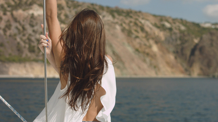 Young beautiful brunette girl on the luxury yacht