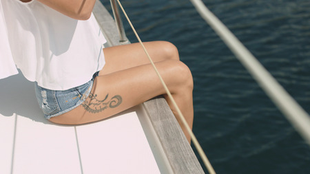 Young beautiful brunette girl sitting on the yacht Stockfoto