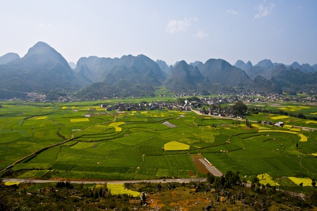 Small Village in Grassland surround with beautiful mountains in Kunming, China.  photo