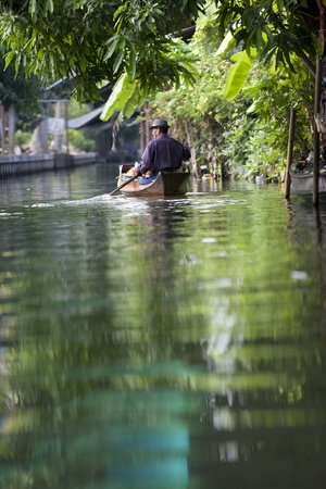 Living and Trading on the River. A man sells noodle on the boat at Damnoen Sauak Floating Market.  photo