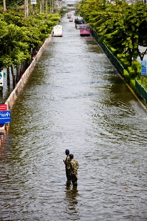 Bangkok, Thailand - November 5, 2011: Two soldiers standby to help people during the flooding in Bangkok.