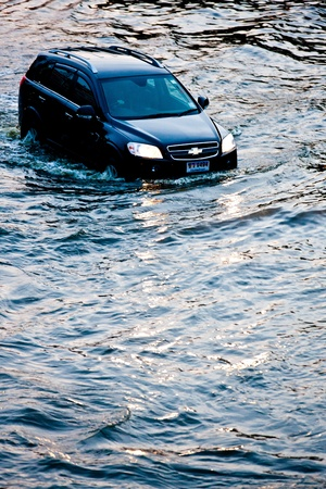 BANGKOK - NOVEMBER 5: Car navigating through the flood on Phahonyothin Road during the worst flooding in Bangkok, Thailand on November 5, 2011.
