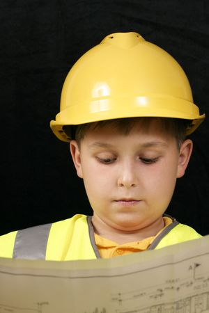 Little foreman reviews some plans.  Focus on boy, plans are oof. Stock Photo - 219571