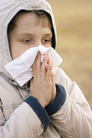 Boy with the sniffles, holding a tissue to his nose photo