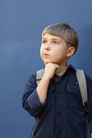observations: Boy with a school backpack and pondering expression - f2.8 Stock Photo