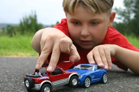 A boy playing with toy cars