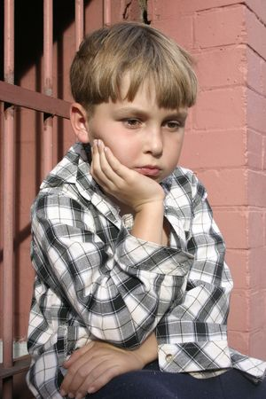 dismal: Boy in mismatched clothing looking sombre.  Part of a kids on the street series Stock Photo