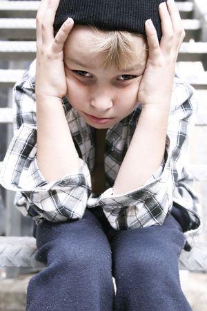 ungeliebt: Deprimiert Stra�e Kind sitzt auf einem Feuer entkommen Treppen grungy backlane