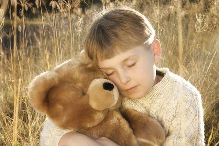 gramineas: Boy abrazos pastos de altura en un osito de peluche.  Foto de archivo