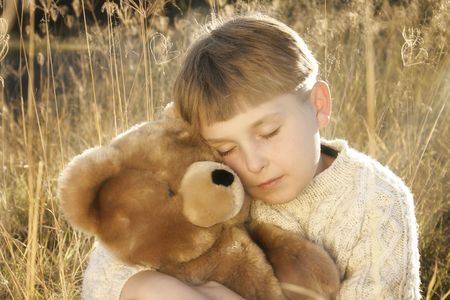 grasses: Boy in tall grasses hugs a teddy bear. Stock Photo