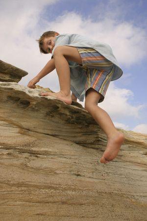 boy barefoot: Child clambering over rocks Stock Photo