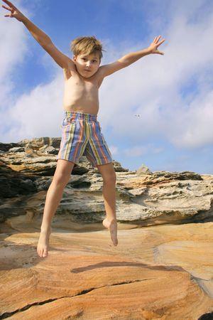 chłopięctwo: Entuzjastyczni dziecka oparzenia off Energy Star skokami. Zdjęcie Seryjne