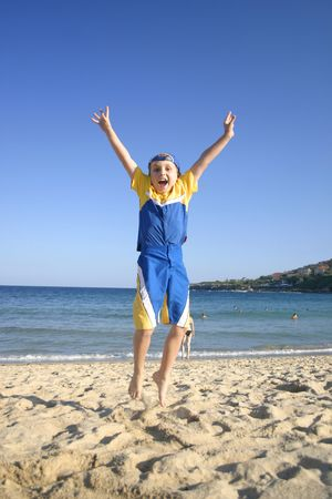 to woo: Woo Yah!   Child leaps into the air on the beach Stock Photo
